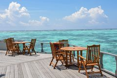 早餐设定了与木桌和椅子在海洋附近 库存图片