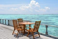 早餐设定了与木桌和椅子在餐馆在海洋附近 免版税图库摄影