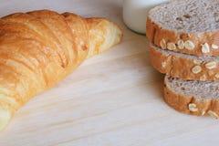 早餐设置了用全麦面包牛奶和新月形面包 库存照片