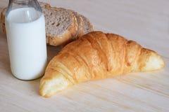 早餐设置了用全麦面包牛奶和新月形面包 免版税库存图片