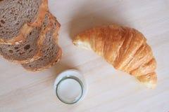 早餐设置了用全麦面包牛奶和新月形面包 免版税图库摄影