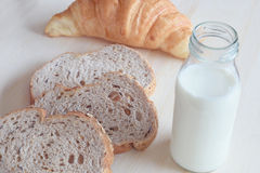 早餐设置了用全麦面包牛奶和新月形面包 免版税库存照片