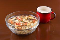 早餐谷物、燕麦粥用脯和坚果在一个玻璃碗和红色杯子挤奶,棕色背景 库存图片