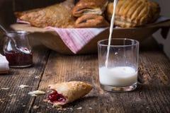 早餐酥皮点心用果酱和牛奶 免版税库存照片