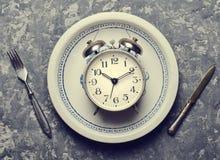 早餐闹钟的时刻在板材、叉子和刀子 库存图片