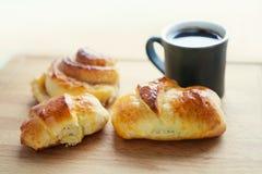 早餐静物画:有卷的咖啡杯,小圆面包,家做了新月形面包 切板背景 侧视图 软绵绵地集中 免版税库存图片