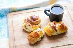 早餐静物画:有卷的咖啡杯,小圆面包,家做了新月形面包 切板背景 看法软的焦点 免版税库存图片