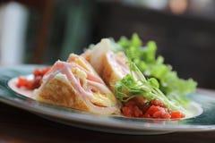 早餐面卷饼火腿和鸡蛋与沙拉葡萄酒样式 免版税库存图片