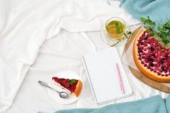 早餐顶视图在床上用莓乳酪蛋糕、薄荷的茶和开放笔记本 库存照片