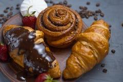 早餐,新鲜的被烘烤的传统新月形面包,在黑纹理背景的板岩盘 r 免版税库存照片