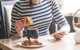 早餐:女孩蘸在一个杯子的一个新月形面包用咖啡,并且在另一只手拿着一个智能手机 早晨明亮的太阳 免版税图库摄影
