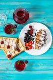 早餐:奶蛋烘饼和新月形面包用蓝莓、樱桃和草莓 在玻璃和蒸馏瓶的被炖的果子 免版税库存照片