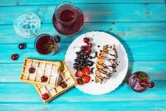 早餐:奶蛋烘饼和新月形面包用蓝莓、樱桃和草莓 在玻璃和蒸馏瓶的被炖的果子 库存图片