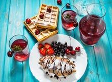 早餐:奶蛋烘饼和新月形面包用蓝莓、樱桃和草莓 在玻璃和蒸馏瓶的被炖的果子 图库摄影