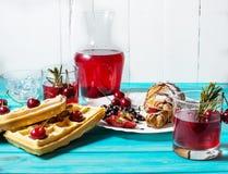 早餐:奶蛋烘饼和新月形面包用蓝莓、樱桃和草莓 在玻璃和蒸馏瓶的被炖的果子 免版税库存图片