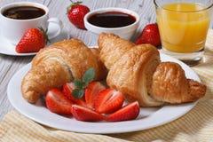 早餐:新月形面包用草莓和咖啡,汁液 库存图片