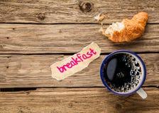 早餐-一个半被吃的新月形面包用浓咖啡 图库摄影