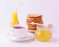 早餐-蜂蜜和堆薄煎饼,茶,在a的橙汁 免版税库存照片