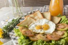 早餐-鸡蛋,三明治,蕃茄,沙拉,调味汁 图库摄影