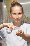 旱田在手中和一个烧瓶用水 免版税库存图片