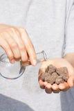 旱田在手中和一个烧瓶用水 免版税图库摄影