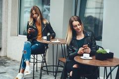 时兴的两个美丽的少妇佩带坐室外在咖啡馆和使用智能手机 免版税库存照片