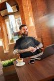 时兴的人微笑的坐在咖啡店 免版税库存图片