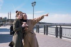 时兴的外套和背包的两个年轻旅客在喀山街道上  看法吸引力 免版税图库摄影