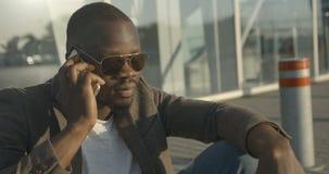 时兴的太阳镜的做迷人的严肃的非洲的人情感地谈话和打手势,当坐路时 股票录像