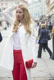 时兴的年轻金发碧眼的女人春天时兴的衣服的和有一个购物袋的在莫斯科的中心 图库摄影
