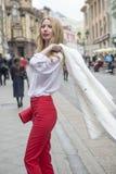 时兴的年轻金发碧眼的女人春天时兴的衣服的和有一个购物袋的在莫斯科的中心 免版税图库摄影