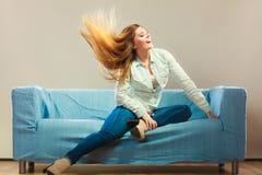 时兴的放松在长沙发的女孩佩带的牛仔布 免版税图库摄影