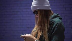 时兴的玻璃和一个帽子的一个时髦的行家女孩使用在智能手机的app在砖紫罗兰墙壁附近 影视素材