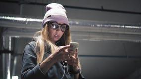 时兴的玻璃的一个时髦的行家女孩使用在智能手机的app 影视素材
