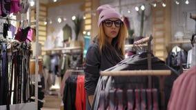 时兴的玻璃的一位年轻行家女性选择新的夹克 商城 影视素材