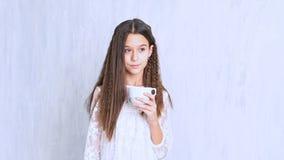 时兴的美丽的女小学生女孩喝热的茶 股票视频