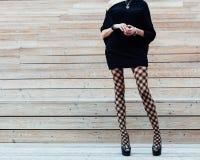 时兴的裤袜、摆在木步的夏天的一件黑礼服和黑高跟鞋的一个长腿的女孩 Fashi 免版税库存图片