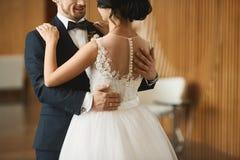 时兴的跳舞的夫妇、英俊的年轻人时髦的衣服的和美丽的深色的式样女孩有婚礼的 库存图片