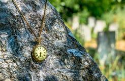 时刻休息在黑大理石墓碑的古色古香的腐朽的怀表在公墓 图库摄影