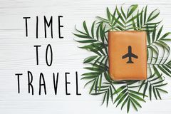时刻旅行在护照的文本与在绿色棕榈叶的飞机 库存图片