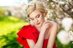 时尚、人们和暑假概念-美丽的晒日光浴在绿色开花的庭院背景的妇女红色礼服 免版税库存图片