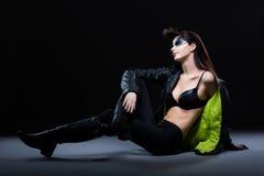 时尚。坐在现代衣物的超现代迷人的妇女。白日梦 免版税图库摄影