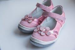 时尚与桃红色花的浅粉红色凉鞋 在白色背景的婴孩孩子` s现代运动鞋鞋子 一个对桃红色 免版税库存照片