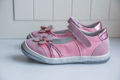 时尚与桃红色花的浅粉红色凉鞋 在白色背景的婴孩孩子` s现代运动鞋鞋子 一个对桃红色 图库摄影