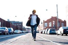 时尚人画象 玻璃的年轻人穿外套步行沿着向下街道的 库存图片