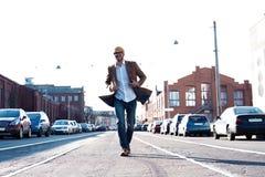 时尚人画象 玻璃的年轻人穿外套步行沿着向下街道的 免版税库存图片