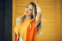 时尚俏丽的妇女穿在黄色木背景的秋天衣裳 免版税库存照片