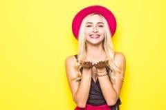 时尚俏丽的妇女送空气穿一件红色帽子和黄色颜色衣裳在五颜六色的黄色背景的甜亲吻 免版税库存图片