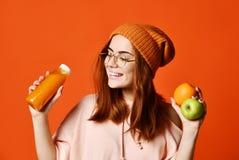 时尚俏丽的年轻女人用新鲜水果汁 库存图片