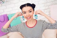 时尚博客作者女孩拿着五颜六色的耳环对照相机 图库摄影